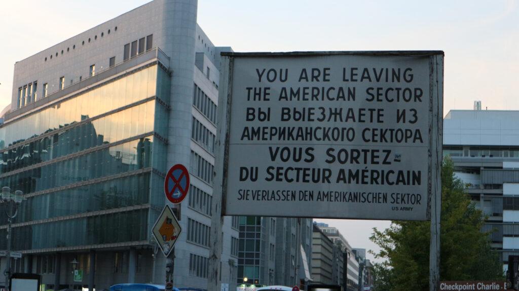 """Het bord bij Checkpoint Charlie. """"You are leaving the American sector"""" Daarna deze zelfde tekst in het Russisch. """"Vous sortez du secteur Américain."""" """"Sie verlassen den Amerikanischen sektor."""" US Army."""