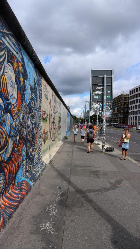 Lopen langs de Eastside Gallery. Een stuk Berlijnse Muur dat onder hande is genomen door diverse kunstenaars.