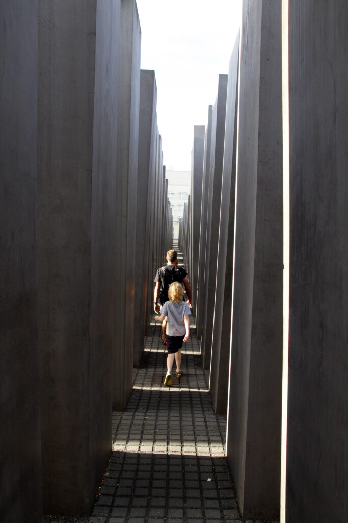 Arjan en Wietse lopen door het holocaust monument. De paden zijn 95 cm breed. Aan weerszijden van hen staan hoge betonblokken. Als je daar tussendoor loopt geeft dat een beklemmend, claustrofobisch en gedesoriënteerd gevoel.