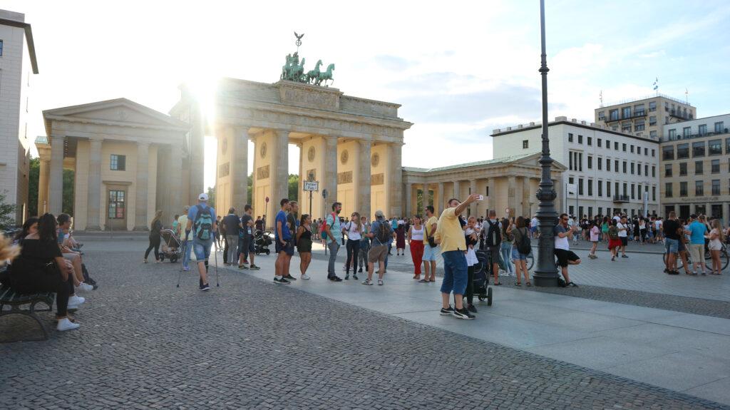 De Brandenburger Tor vanaf de Pariser Platz. Het is avond en niet superdruk. Verschillende toeristen staan voor de Tor en maken selfies of nemen foto's. Voor veel toeristen een hoogtepunt van hun bezoek aan  Berlijn en in onze lijst op nummer 2.