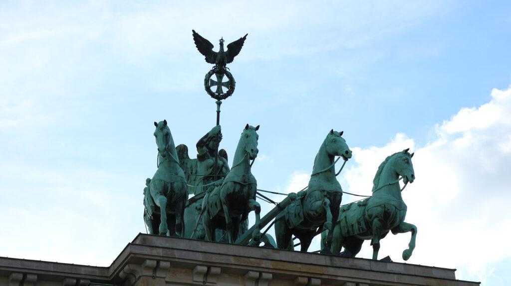 Bovenop de Brandenburger Tor staat de Quadriga. Een strijdkar met vier strijdrossen in brons. De Veldheer houdt een vaandel vast wat heel erg doet denken aan het Nationaal Socialisme in Duitsland tijdens de Tweede Wereldoorlog. Deze foto is een close up van de Quadriga.