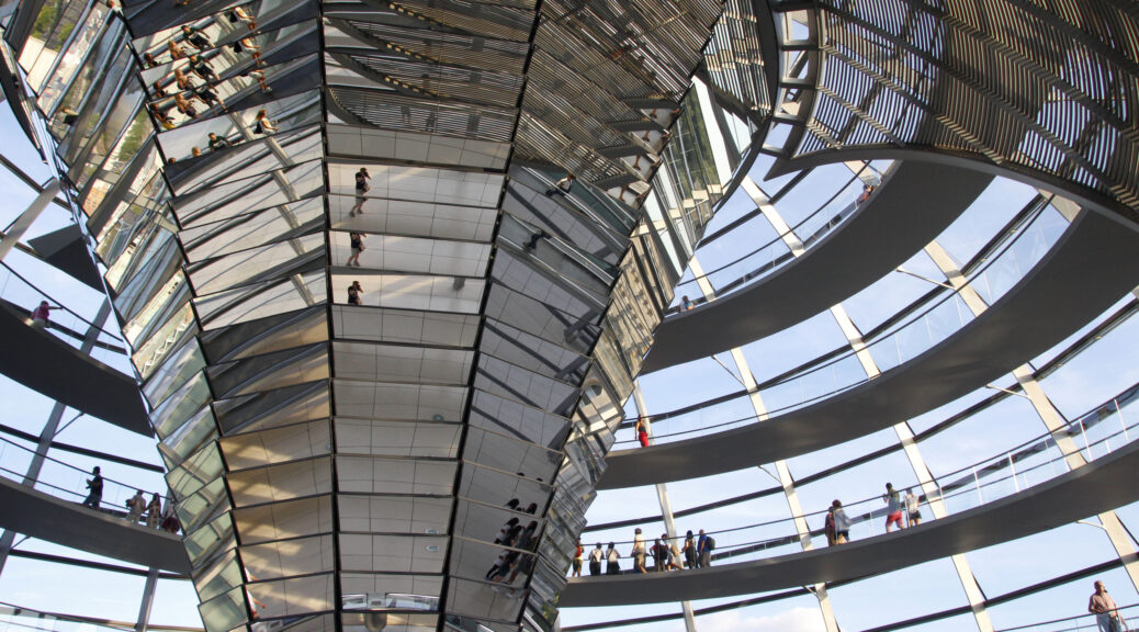 Binnenin de Reichstagkoepel. De koepel is volledig gemaakt van glas en loopt rond. In het midden loopt een pilaar van smal beneden naar breed omhoog. Deze pilaar is bedekt met spiegels. Hierdoor heeft dat een mooi beeldeffect.