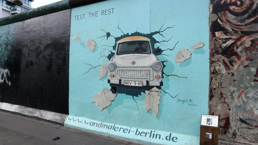 Een beschildering op de Berlijnse Muur. Een Trabantje met het kenteken November 9, 89 ( de dag waarop de Muur viel) rijdt dwars door de Berlijnse Muur heen.