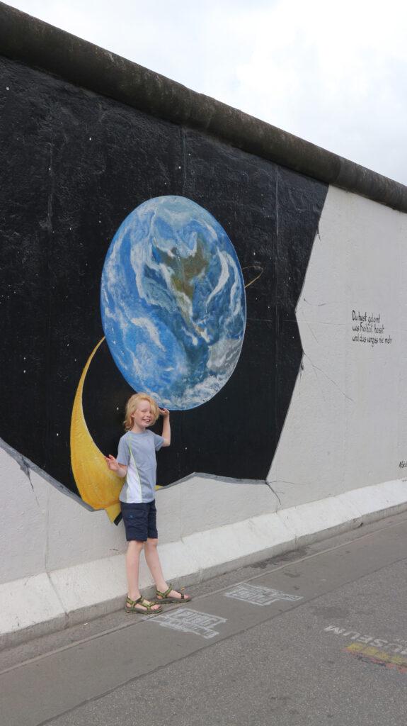 Wietse staat bij een gedeelte van de De Muur in Berlijn die nog in tact is. Hier is een wereldbol op geschilderd. Hij houdt zijn hand net onder de wereld, zodat het lijkt of hij de wereld in zijn hand heeft.