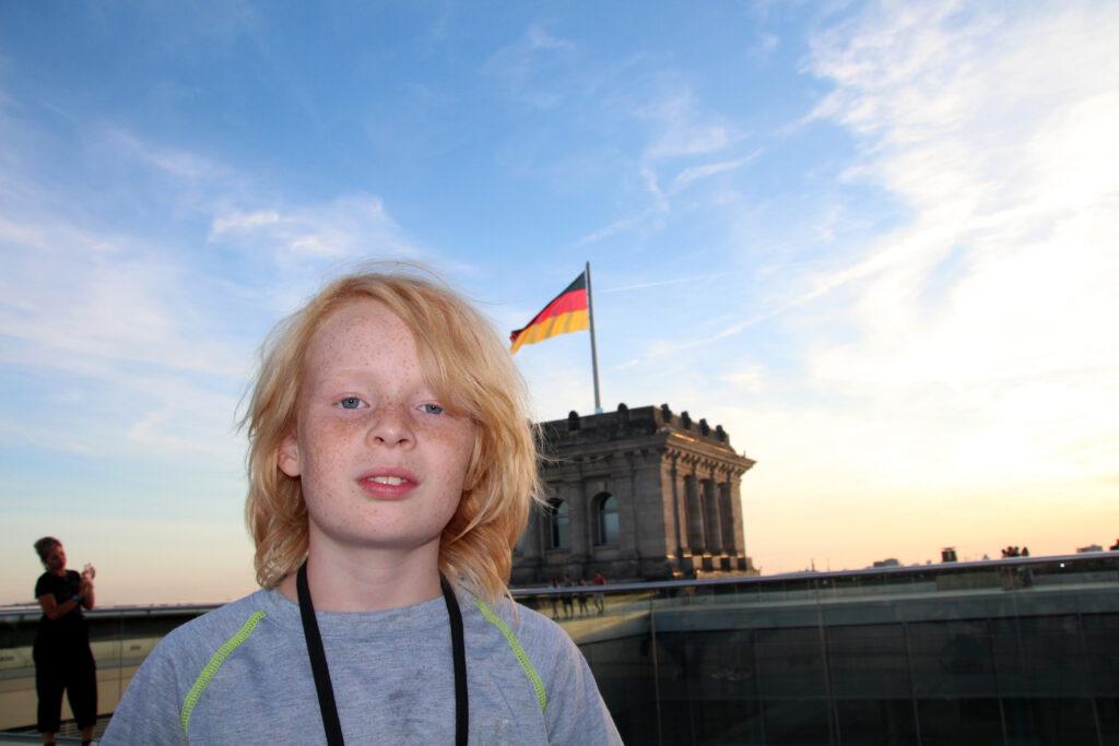 Wietse staat op het dak van de Reichstag met op de achtergrond de Duitse vlag.