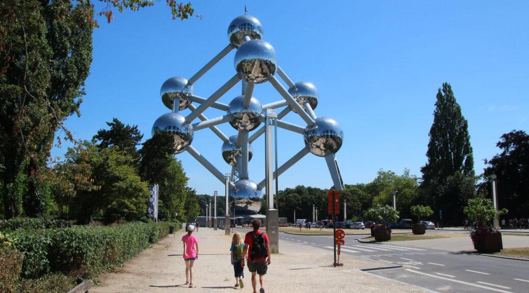 Het Atomium in Laken, Brussel. We lopen recht op dit bijzondere gebouw af. Het gebouw heeft de vorm van een ijzeratoom met 9 bollen die onderling met elkaar in verbinding zijn. Dit alles gemaakt van glimmend metaal met een fel zonnetje maakt dat het gebouw schittert.
