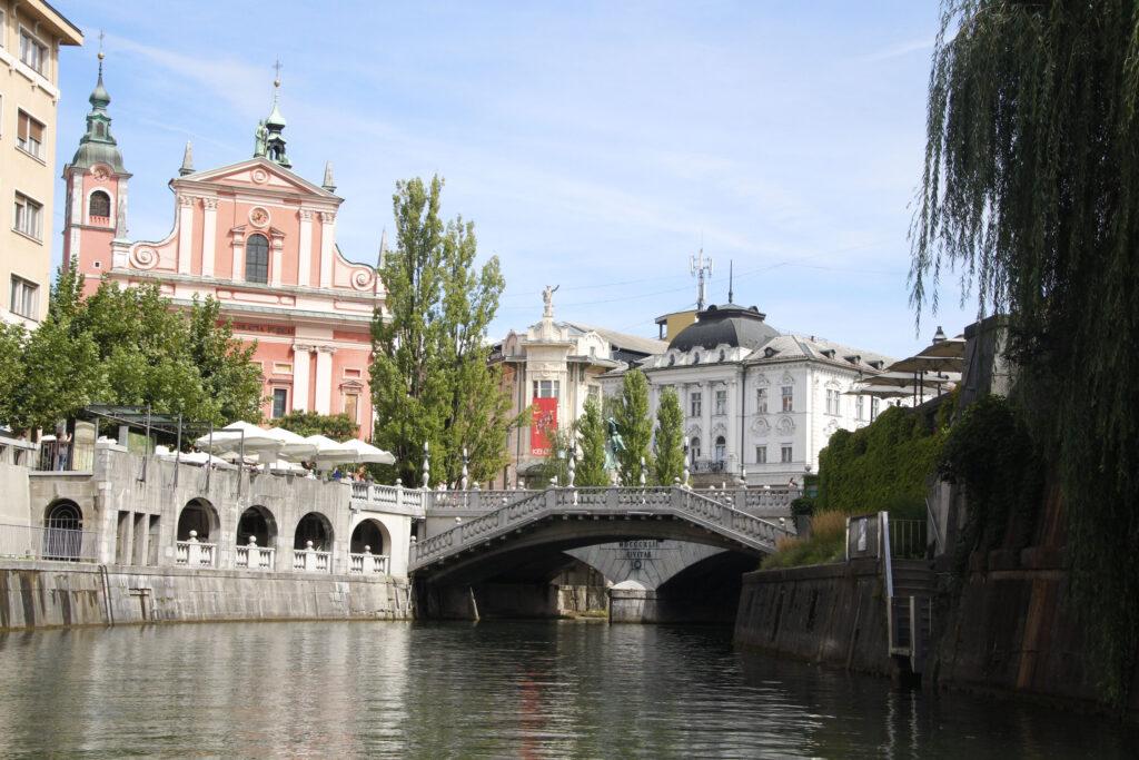 Zicht vanaf het water op het roze Franciscanenklooster en de Triple Bridge
