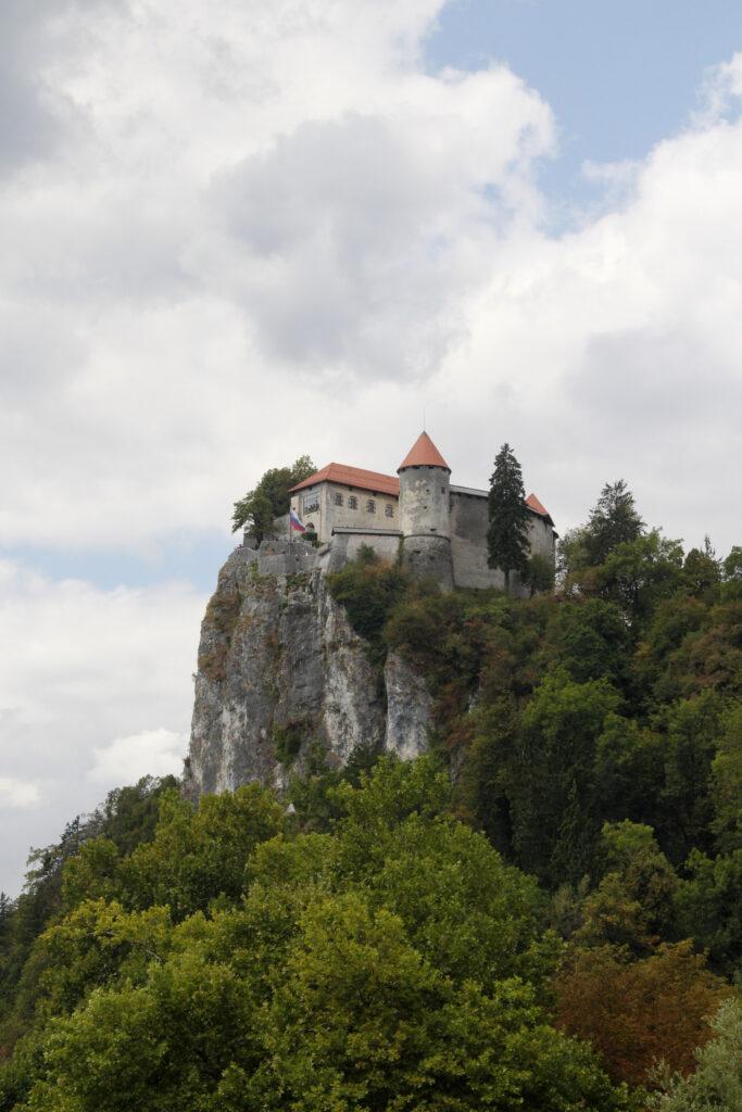 Hoog bovenop de rotsen ligt Kasteel Bled. Kasteel Bled kijkt uit over het Meer en het dorp Bled.