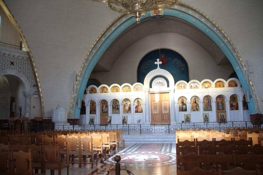 Het altaar van de orthodoxe kerk. Links het doopvond. Een breed middenpad met aan weerszijden houten stoelen. Op het altaar zijn schilderingen van diverse heiligen te vinden.