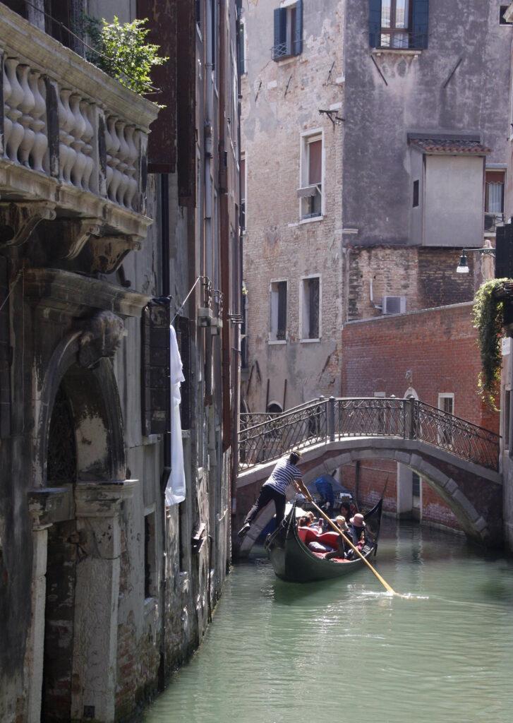 Een eenzame gondel door het azuurblauwe water van Venetië zet zich met zijn been af tegen de huizen om wat vaart te maken voor het naderende bruggetje.