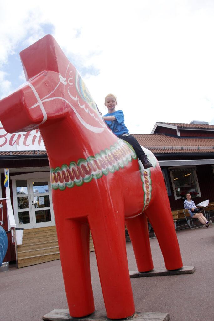 Wietse zit op een reusachtig groot, rood Dalapaard bij Grannas A. Olsson Hemslöjd Ab.