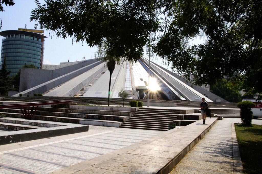De Piramide van Tirana wat dichterbij. De zon weerkaatst op het glas en verblind je bijna.