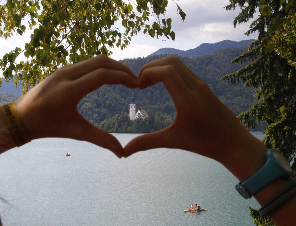 Zicht op de Maria Hemelvaartskerk op een klein eilandje in Het Meer van Bled. Marije heeft haar handen tot een hartje gevormd en in dat hartje kijk je op het kerkje.