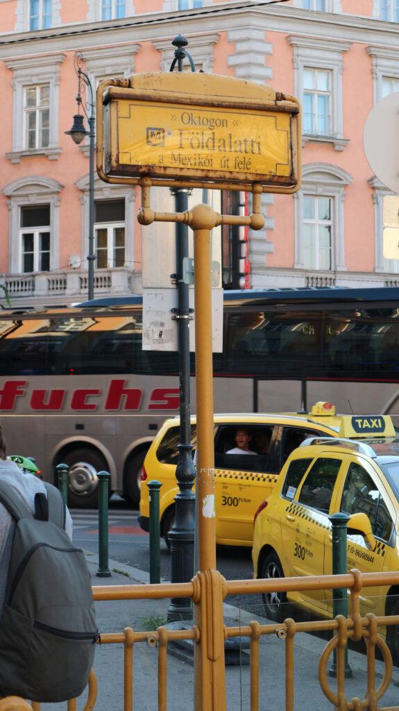 Geel bord Metro Földalatti met een paar taxi's wachtend op klanten.