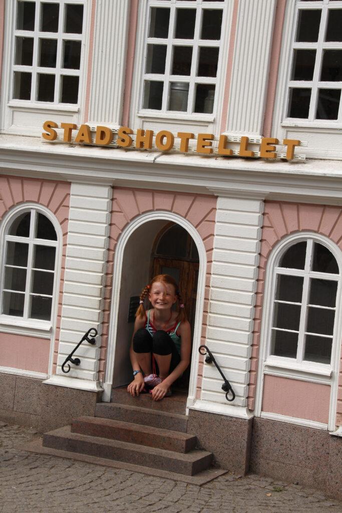 Marije zit op haar hurken in de deuropening van het Stadshotel. Dit past net aan. Dit bouwwerk maakt deel uit van het Kleine, Kleine Dorp in Astrid Lindgrens Värld