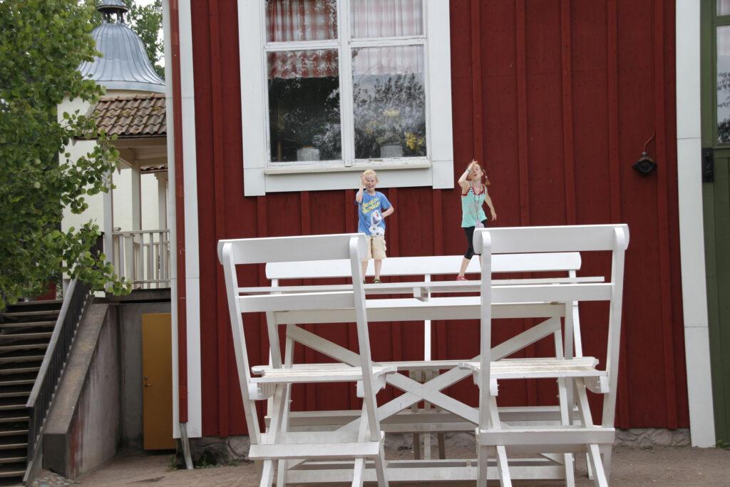 Marije en Wietse spelen in Astrid Lindgrens Värld. Ze staan op een grote terrastafel (ze lijken zo klein als elfjes) en trekken gekke bekken. Bij de tafel hoort een bankje en twee terrasstoelen. Dit alles staat voor een gigantisch huis, Falunrot geschilderd.