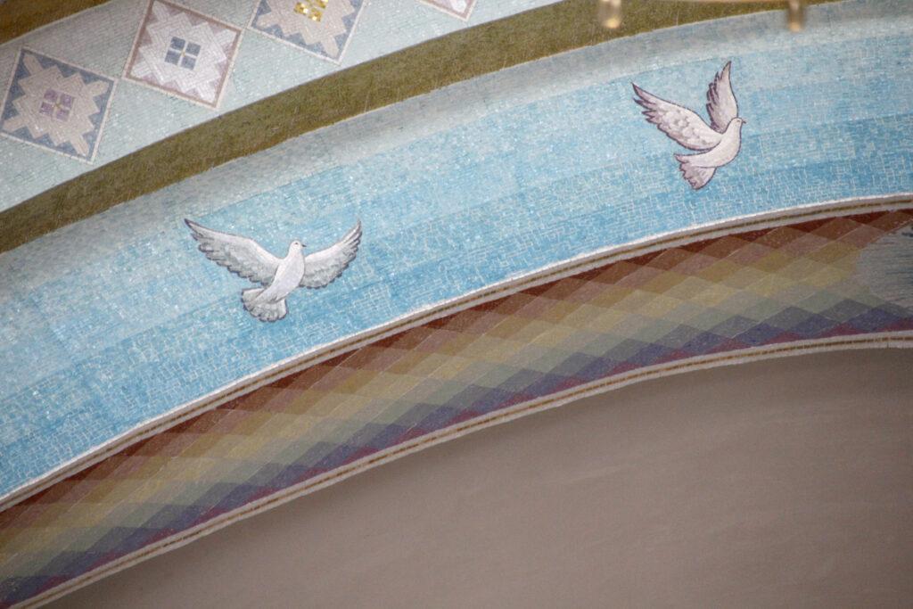 Detail van de boog die over het altaar heen loopt. De voorkant van de boog in blauw met beschilderde witte duiven. De onderkant van de boog bestaat uit een regenboog in ruitpatroon.