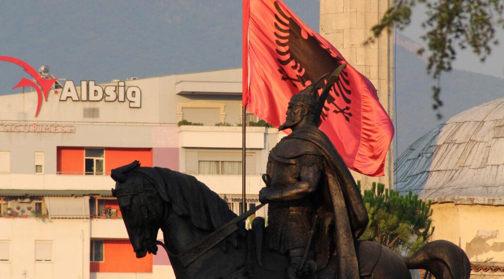 Het beeld van Skanderbeg, de held die de Ottomanen uit Albanië verdreef. Op de achtergrond de Albanese vlag.