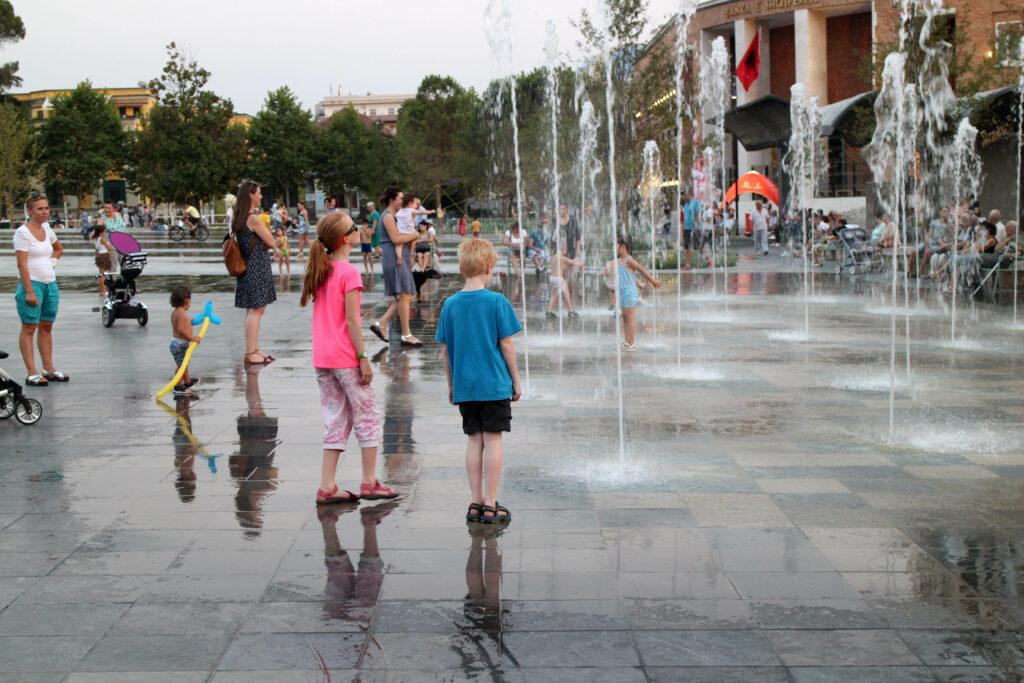 Marije en Wietse staan 's avonds bij de fonteinen die uit de tegels omhoog komen op het Skanderbegplein in Tirana. Er spelen al kinderen in de fonteinen.