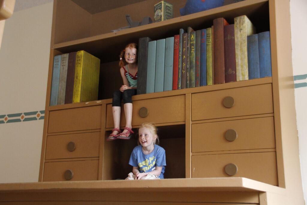 Marije zit op een plank naast levensgrote boeken. Wietse zit daaronder in een open kastje, net onder een laatje.