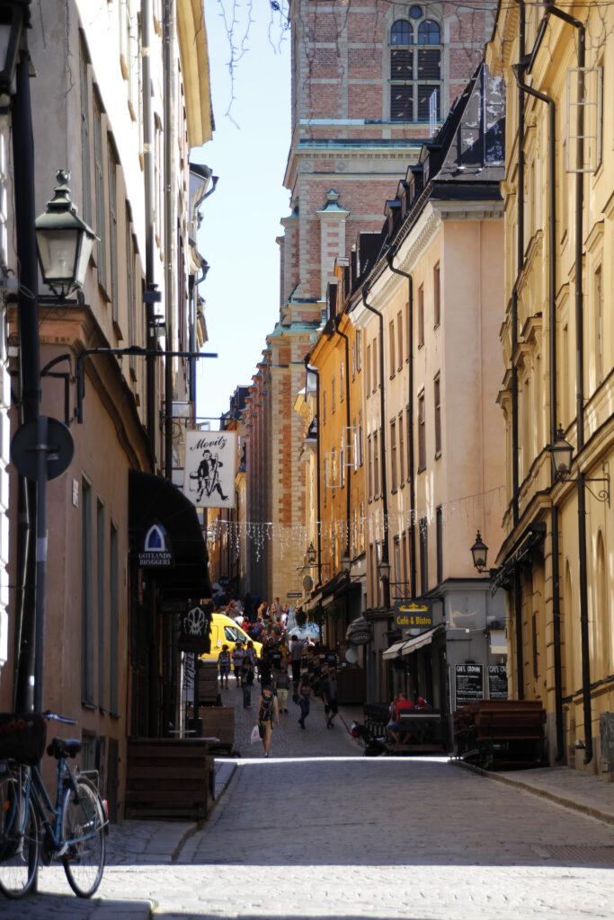 Smalle straat, met hoge lichtgele gebouwen in het oude gedeelte van Stockholm. In de volksmond Gamlastan genoemd.