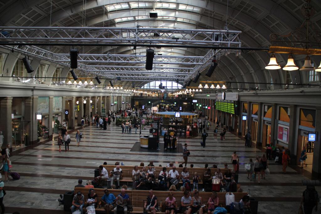 Drukte op het prachtige centraal station van Stockholm. Het stationsgebouw loopt met een boog en heeft op het hoogste punt een rij dakramen waardoor licht naar beneden valt.