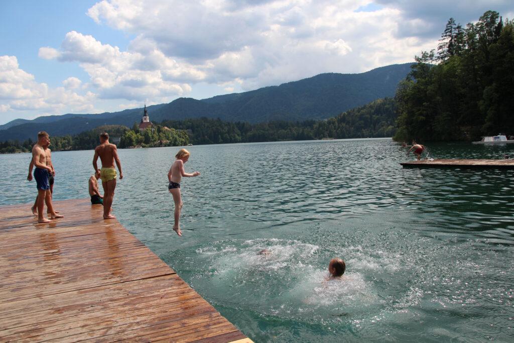 Mensen zwemmen bij de steigers van de roeivereniging. Vanaf hier een mooi zicht op de Maria Hemelvaartskerk bij het Meer van Bled.