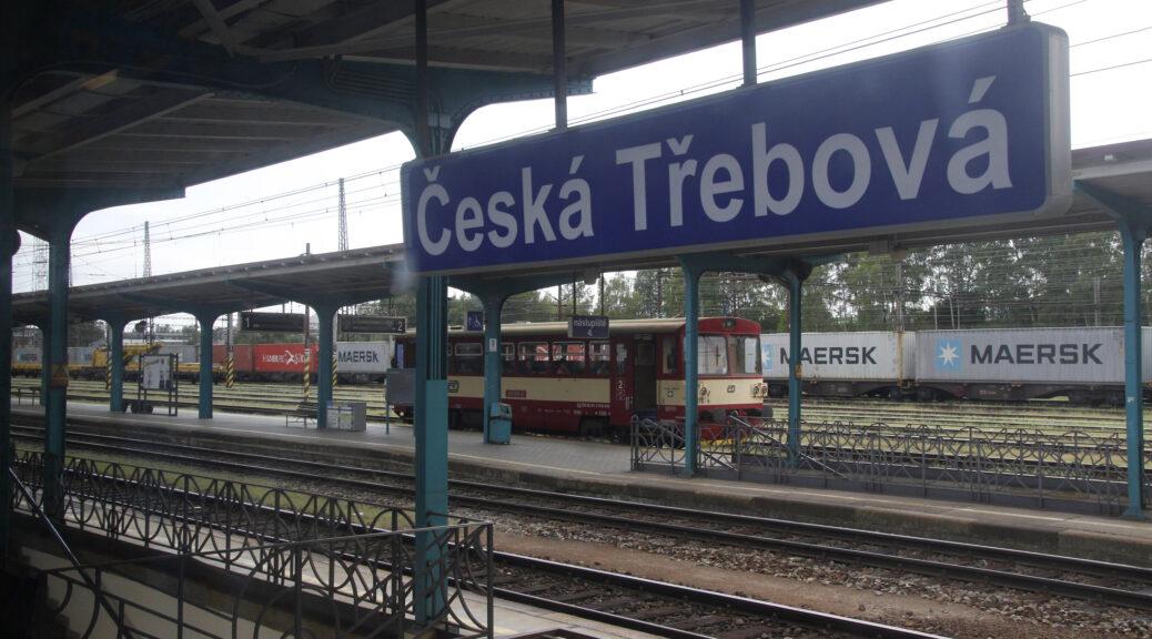 Een blauw plaatsnaambordje met een onuitspreekbare naam op een station in Tsjechië. Op de achtertrond een goederentein.