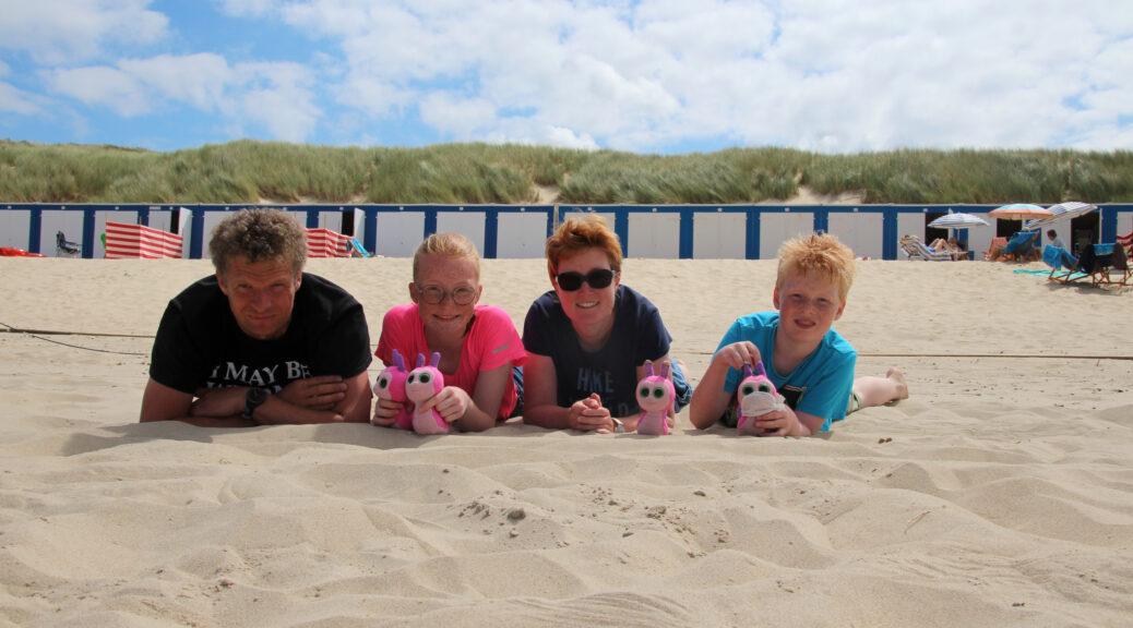 Arjan, Marije, Annika en Wietse op hun buik in het zand. Voor een rij strandhuisjes en de duinen.