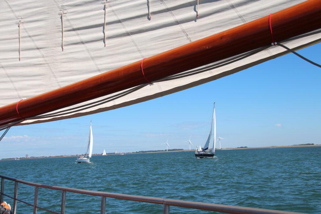 Zeilboten op de Oosterschelde gezien vanaf een zeilboot net onder het zeil door.