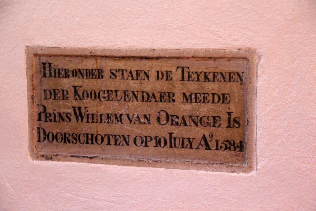 """Bord dat hangt bij de kogelgaten van de kogels waar de prins van Oranje mee is vermoord. De tekst luidt als volgt: """"Hier onder staen de teykenen der Koogelendaer meede Prins Willem van Orange Is Doorschoten op 10 Iuliy Anno Domini 1584."""