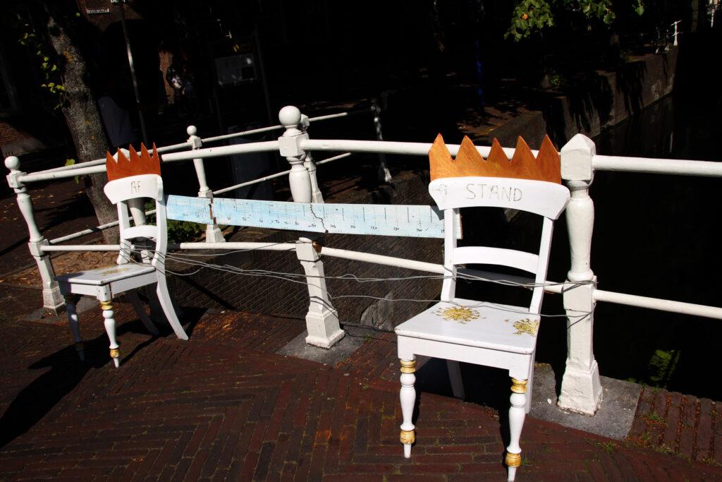 Anderhalve meter afstand-kunst in het centrum van Delft. Twee houten stoelen met een meetlat van anderhalve meter ertussen.