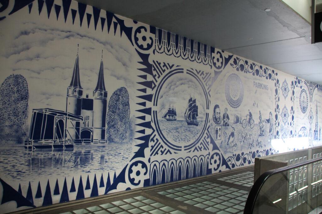 Parkeergarage Zuidpoort in Delft. De muren zijn met Delfts Blauwe graffiti beschilderd met Hollandse taferelen. Zeilboten, Willem van Oranje, Kievietseieren, fietsers.