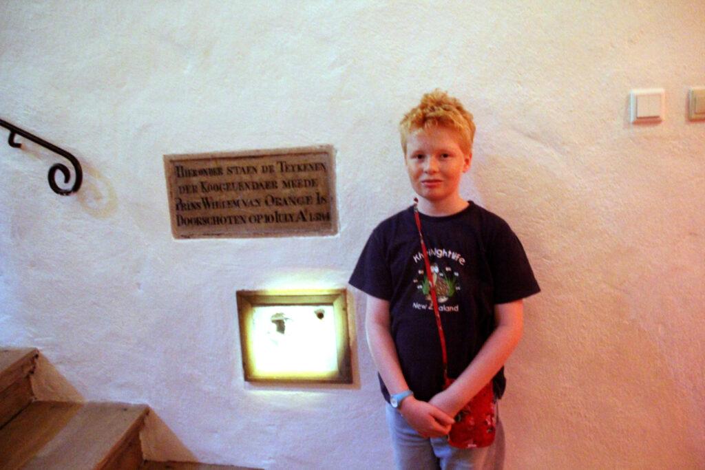 Wietse op de plaats delict. Hier is honderden jaren geleden prins Willem van Oranje neergeschoten. De kogelgaten zitten nog steeds in de muur.