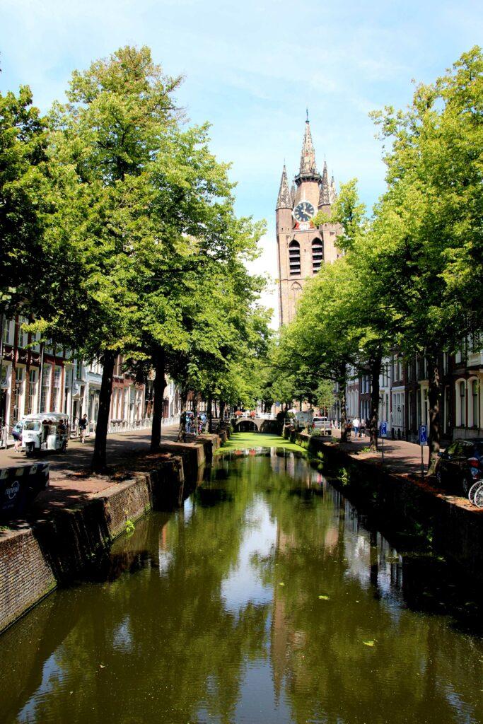 Zicht op de Oude Kerk in Delft vanaf een bruggetje over de gracht heen.