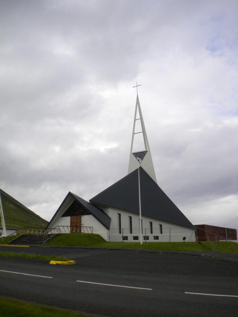 De Ólavsvíkkurkirkja in Ólavsvík springt door zijn stijl erg op in het landschap.