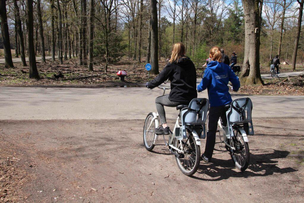De meeste witte fietsen hebben een kinderzitje. Door het park staan ANWB paddenstoelen met de route.
