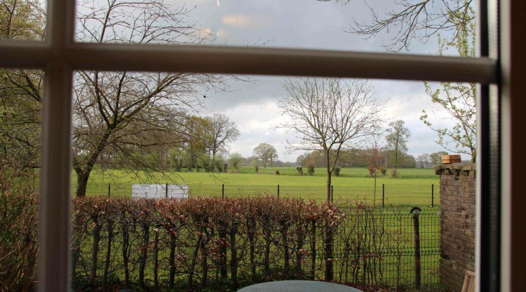 het weidse Achterhoekse landschap gezien door een raam.