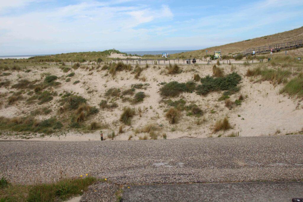 Op de voorgrond het asfalt van de Hondsbossche Zeewering, daarachter de Hondsbossche Duinen met daarachter weer het strand.