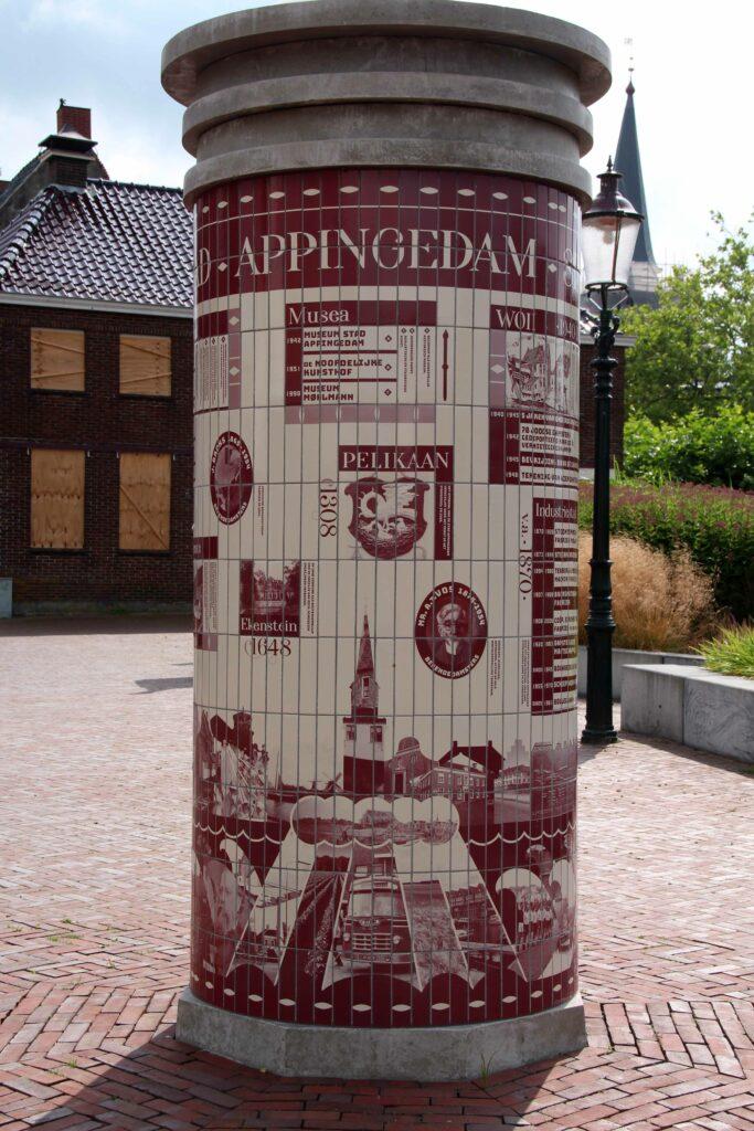 Zuil met de geschiedenis van Appingedam in tegeltjes.